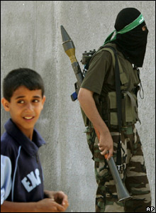 Palestinian boy stands in front of militant