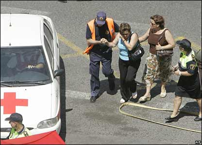 Two women, believed to be relatives or friends of the crash victims, are led away from the scene medics