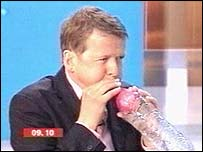Bill Turnbull blowing up a balloon in a bottle