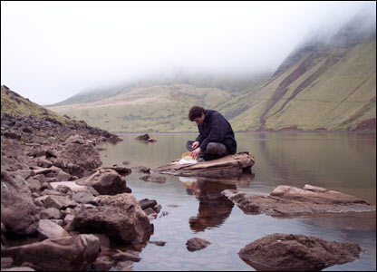 Stephen Coates cutting bread by Pen y Fan, Brecon Beacons (Ben Cramp)