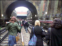 Commuters walk down tube tracks