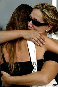 Women hug outside Valencia's Colon metro station during the silence