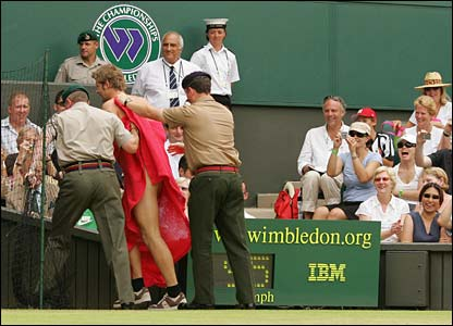 A streaker is removed from Centre Court by security