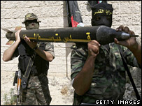 Palestinian militants with Qassam rocket