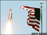 Shuttle Discovery lifts off with US flag in the foreground