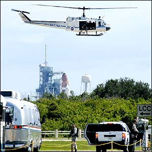 Security helicopter watches over the van taking the crew to the launch pad