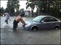 Residents push a car caught in the flood