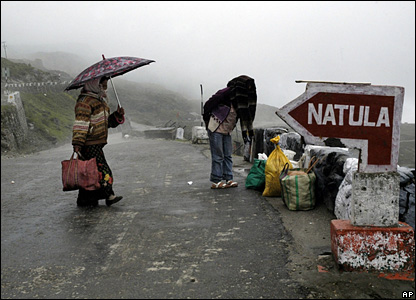 People walk with their belongings on a road close to the India-China border outpost in Nathu La Pass.