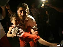 Palestinian medic carries injured child to safety after Gaza City air strike
