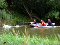 A lifeboat crew chase the injured swan around the lake