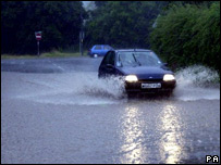 A car driving through flash flooding in Congresbury, Somerset