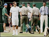 Roger Federer watches the protestors being taken away