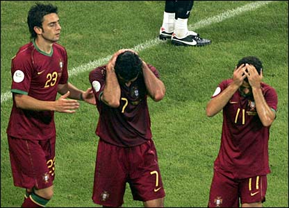 Portugal players hold their faces after Luis Figo misses