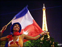 Woman waves tricolour in front of Eiffel Tower