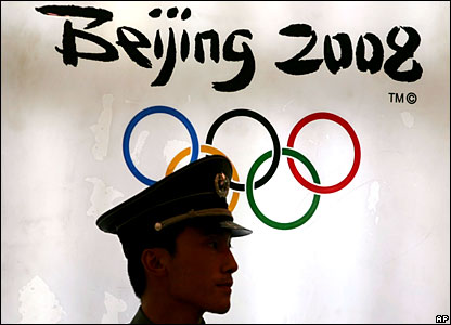 A Chinese official in front of the Olympic logo