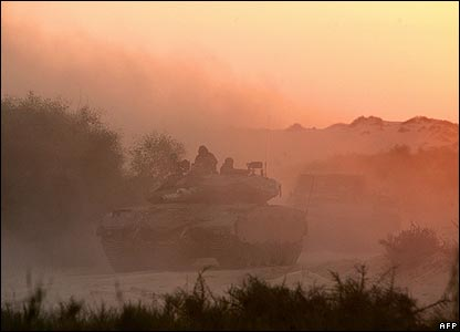 Israeli tanks and armoured personnel carriers (APCs) cross the border into the Gaza Strip from the Kibbutz of Zikim at sunrise