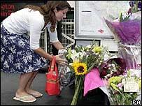 Mujer depositando flores en la estación de bus de Edgware Road.