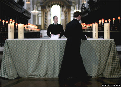 Priests lighting candles in St Paul's Cathedral