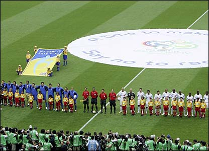 The two teams line up to sing their national anthems