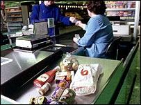 A till assistant receives money from a shopper