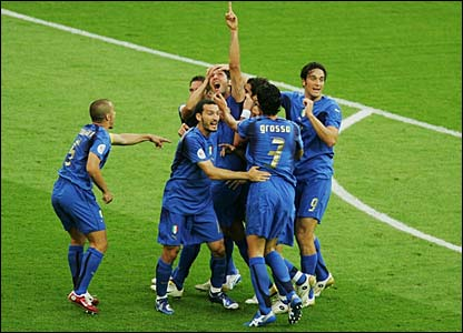 Marco Materazzi points to the sky as he is surrounded by team-mates