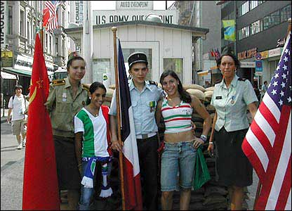 Fans pose in front of Checkpoint Charlie, Berlin