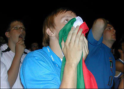 An Italy fan watches anxiously as the game goes to penalties