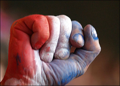 A red, white and blue painted clenched fist punches the air