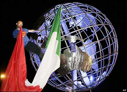 An Italian fan attaches the Italian flag to an illuminated globe