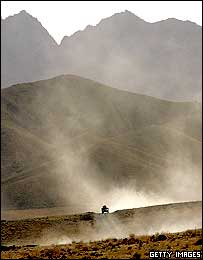 A US military vehicle drives through mountainous Afghanistan landscape