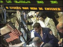Trabajadores y pantalla de la Bolsa de Nueva York.