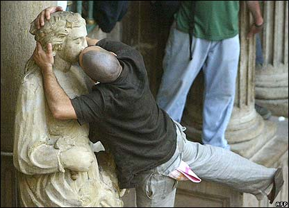 Man kisses a statue in Pamplona.