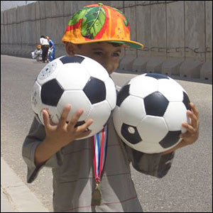 Mark sends in this photo of a young boy holding two footballs in Iraq before the Italy v France final
