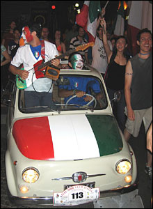 An Italian fan drives a small car, as the passenger plays guitar throughout packed Turin streets