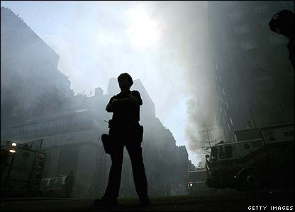 A policeman stands guard in a dust-filled street
