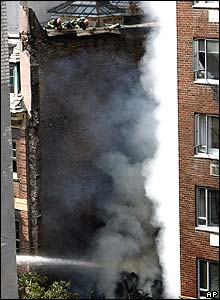 Firefighters on the roof of the next building examine the damage