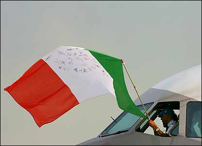The plane's pilot waves an Italian flag from the cockpit