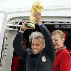 Cannavaro lifts the World Cup as the team arrive in Italy