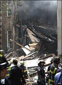 Front view of collapsed building with fire fighters in front