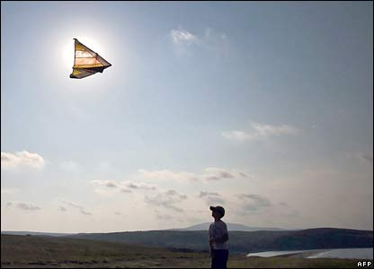 A boy flies his kite into the setting sun