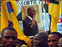 Joseph Kabila supporters hold banners during the official launch of the Alliance for the Presidential Majority