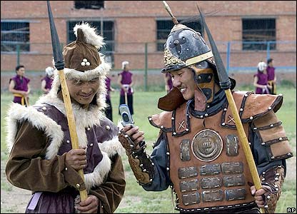 Soldiers share a joke on a mobile phone while wearing traditional Mongol costumes