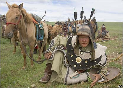 Mongolian soldier rests by his horse as he prepares to re-enact a battle