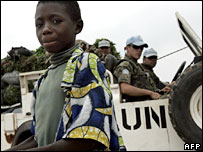 UN peacekeepers behind a Congolese boy