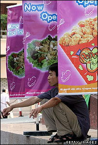 A man sits among fast food posters outside a newly opened restaurant in downtown Hanoi 22 June 2006. This is the first ever US fast food shop to be opened in northern Vietnam
