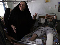 A woman grieves at her wounded son's bedside