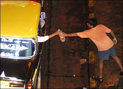 Man hands a bottle of water to a bus passenger (Image: Urdu Times)
