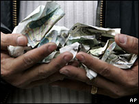 Person holding crumpled �5 notes