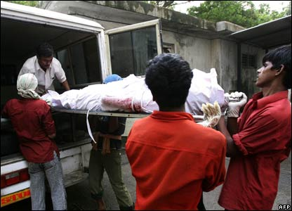 A victim of the trains blasts is moved from the mortuary of Bhabha hospital