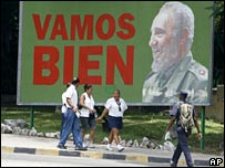 "People walk past a poster showing Fidel Castro and the words ""We're doing fine"" in Havana"